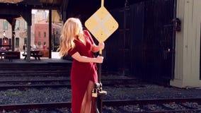 Femme blonde dans la robe rouge se tenant dessus pour railroad le signe banque de vidéos