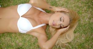 Femme blonde dans le bikini blanc se trouvant sur l'herbe banque de vidéos