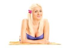 Femme blonde dans le bikini se trouvant sur une serviette Image libre de droits