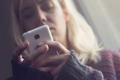 Femme blonde dans le chandail foncé regardant son téléphone images libres de droits