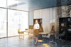Femme blonde dans le coin de bureau gris et en bois image libre de droits