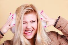 Femme blonde dans les bouche-oreilles et la veste d'hiver image libre de droits