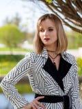 Femme blonde dans un manteau noir et blanc image libre de droits