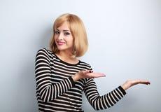 Femme blonde de beau maquillage tenant et présent quelque chose dedans Photographie stock