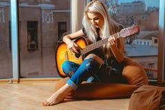Femme blonde de beauté essayant de jouer la guitare Photos stock