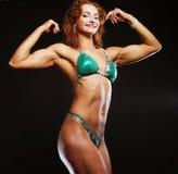 Femme blonde de bodybuilder dans le bikin sur le fond noir Image libre de droits