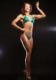 Femme blonde de bodybuilder dans le bikin sur le fond noir Photos libres de droits