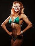 Femme blonde de bodybuilder dans le bikin sur le fond noir Photographie stock libre de droits