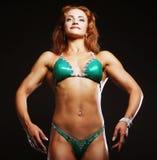 Femme blonde de bodybuilder dans le bikin sur le fond noir Images libres de droits