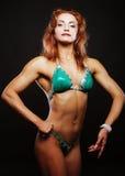 Femme blonde de bodybuilder dans le bikin sur le fond noir Images stock