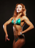 Femme blonde de bodybuilder dans le bikin sur le fond noir Photo libre de droits