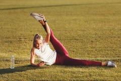 Femme blonde de forme physique s'étirant sur l'herbe photographie stock
