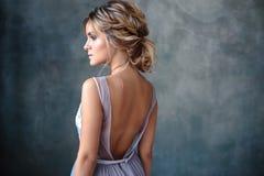 Femme blonde de jeune mariée dans une robe de mariage moderne de couleur avec la coiffure élégante et composer Verticale de beaut image libre de droits