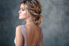 Femme blonde de jeune mariée dans une robe de mariage moderne de couleur avec la coiffure élégante et composer Verticale de beaut photographie stock libre de droits