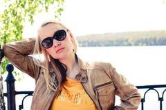 Femme blonde de mode dans la veste en cuir brun clair et des lunettes de soleil posant devant le lac photo stock