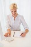 Femme blonde de sourire à l'aide de l'ordinateur Photographie stock libre de droits