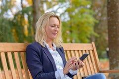 Femme blonde de sourire à la mode employant son mobile images libres de droits