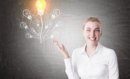 Femme blonde de sourire, arbre d'ampoule Image libre de droits