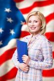 Femme blonde de sourire attirante devant le drapeau des Etats-Unis Photos libres de droits
