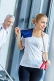 Femme blonde de sourire avec la serviette et la corde à sauter regardant loin dans le gymnase images libres de droits