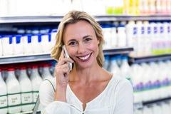 Femme blonde de sourire ayant un téléphone d'appel Photographie stock