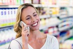 Femme blonde de sourire ayant un téléphone d'appel Images stock