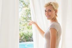 Femme blonde de sourire de portrait montrant dehors Image stock
