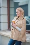 Femme blonde de sourire faisant une pause pour une tasse de café images stock