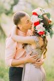 Femme blonde de sourire heureuse dans la chemise de port de baiser lilas de pêche d'homme bel de robe et de guirlande Photographie stock
