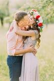 Femme blonde de sourire heureuse dans la chemise de port de baiser lilas de pêche d'homme bel de robe et de guirlande Images libres de droits