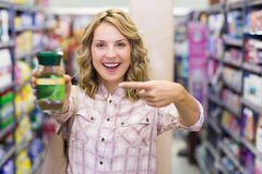 Femme blonde de sourire heureuse montrant un produit Photo libre de droits