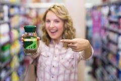 Femme blonde de sourire heureuse montrant un produit Photographie stock