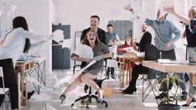 Femme blonde de sourire heureuse ROUGE d'affaires d'EPIC-W ayant l'amusement avec des collègues de bureau jetant le papier sur le clips vidéos
