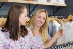 Femme blonde de sourire montrant des vêtements à son ami Image stock