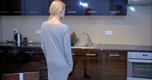 Femme blonde de sourire posant à la cuisine banque de vidéos