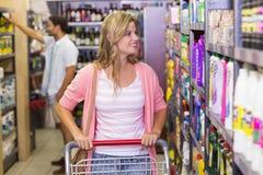 Femme blonde de sourire regardant l'étagère Photo stock
