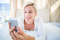 Femme blonde de sourire se trouvant sur le lit et textotant avec son téléphone portable image stock