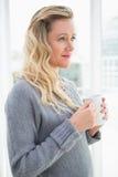 Femme blonde de sourire tenant la tasse de café regardant loin Photo stock