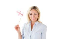 Femme blonde de sourire tenant le drapeau anglais Photographie stock libre de droits