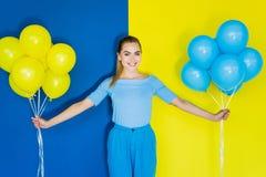 Femme blonde de sourire tenant les ballons bleus et jaunes sur le bleu photo stock
