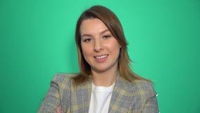 Femme blonde de sourire tenant les bras croisés et regarder la caméra au-dessus du fond vert banque de vidéos