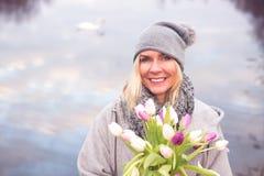 Femme blonde devant le lac avec des tulipes photos stock