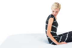 Femme blonde douteuse s'asseyant sur le lit Photographie stock libre de droits