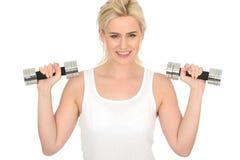 Femme blonde en bonne santé d'ajustement heureux attrayant jeune établissant avec les poids muets de Bell Photographie stock libre de droits
