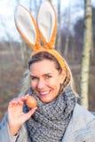 Femme blonde en parc avec des oreilles de lapin tenant un oeuf photos stock