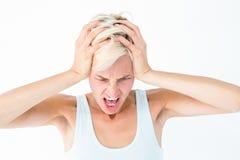 Femme blonde fâchée criant et tenant sa tête images stock