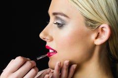 Femme blonde faisant composer ses lèvres par le maquilleur Photo libre de droits