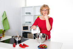 Femme blonde faisant cuire et faisant cuire au four dans la cuisine Photos stock