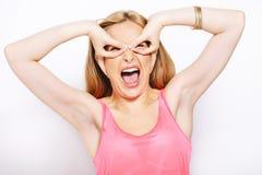 Femme blonde faisant des expressions drôles d'isolement sur le blanc Photographie stock libre de droits