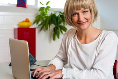 Femme blonde faisant face à l'appareil-photo tout en travaillant sur l'ordinateur portable Image stock
